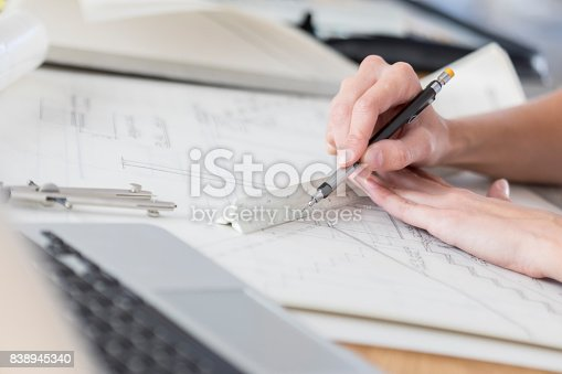istock Closeup of human hands using an architect's scale to draw on blueprint 838945340