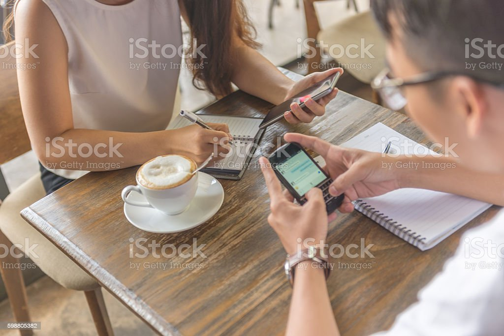 Close-up of human hands using smartphone while writing note stock photo