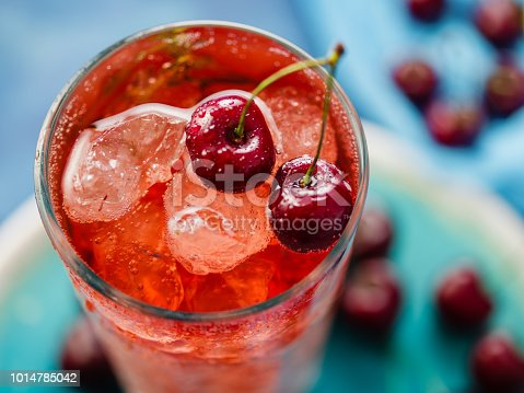 CLose-up of Iced organic cherry lemonade with fresh berries on the blue table, top view.