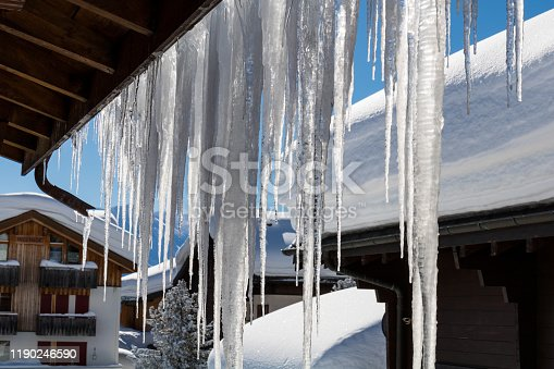 Close-up of icicles in front of blue clear sky in winter time with snow covered log cabin in the background