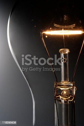 Close-up of illuminated light bulb against gradation background.