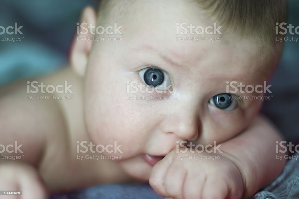 Close-up of infant boy with head resting on arm stock photo