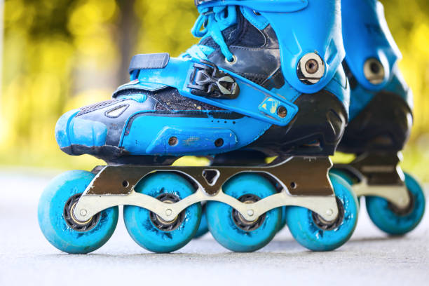 Closeup of inline roller skates with blue wheels. stock photo
