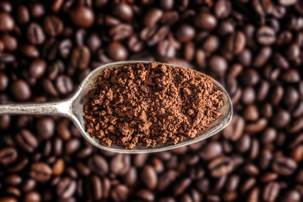 close-up of instant coffee in a spoon with roasted coffee beans at the background - café solúvel imagens e fotografias de stock