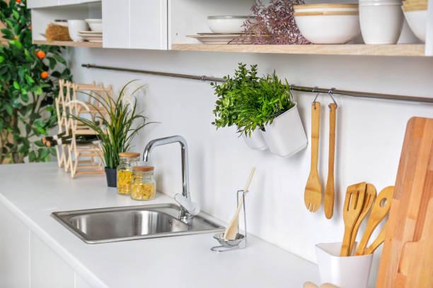 nahaufnahme des inneren der moderne weiße küche mit hölzernen küchenutensilien und mandarin baum im hintergrund - küche deko grün stock-fotos und bilder