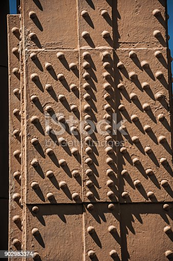 istock Close-up of iron plates and rivets from the top of the Eiffel Tower with sunny sky in Paris. 902983374