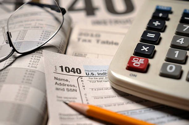 """Close-up of IRS Form 1040 """"1040 confusion and complexities; selective focus on 1040 form, with eyeglasses, calculator and pencil slightly softened"""" 1040 tax form stock pictures, royalty-free photos & images"""