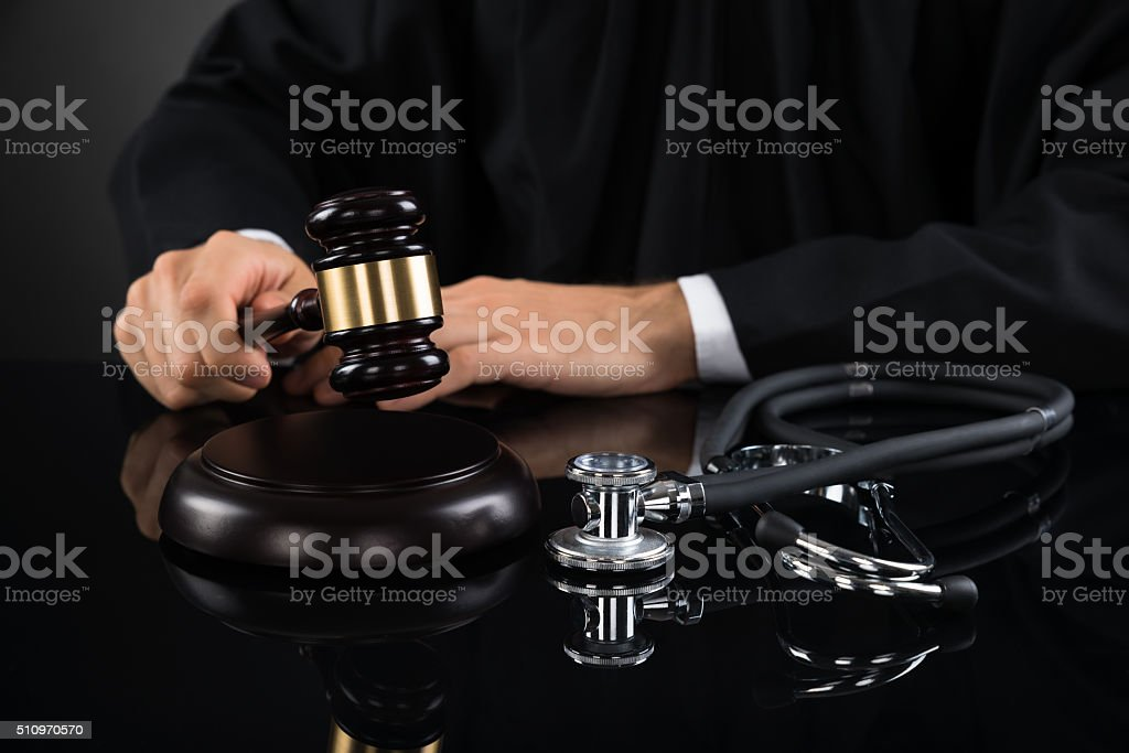 Close-up Of Judge Hitting Gavel With Stethoscope stock photo