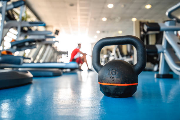 Close-Up of Kettlebell and Fitness Enthusiast in Background stock photo