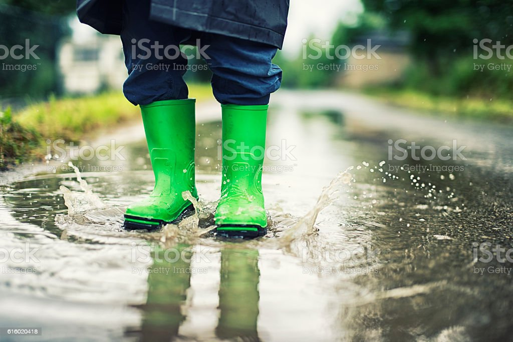 Closeup of kid's galoshes splashing in street puddle stock photo