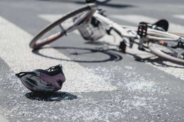 Closeup of kid's helmet and bike on a pedestrian lines after danger incident with a car Closeup of kid's helmet and bike on a pedestrian lines after danger incident with a car misfortune stock pictures, royalty-free photos & images