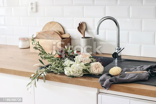 Closeup of kitchen interior. White brick wall, metro tiles, wooden countertops with kitchen utensils. Roses flowers in black sink. Modern scandinavian design, home staging, cleaning concept.