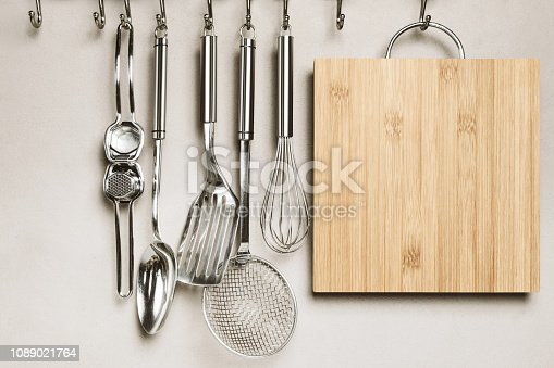 Kitchen detail, utensils for cooking hanging with hooks on the wall