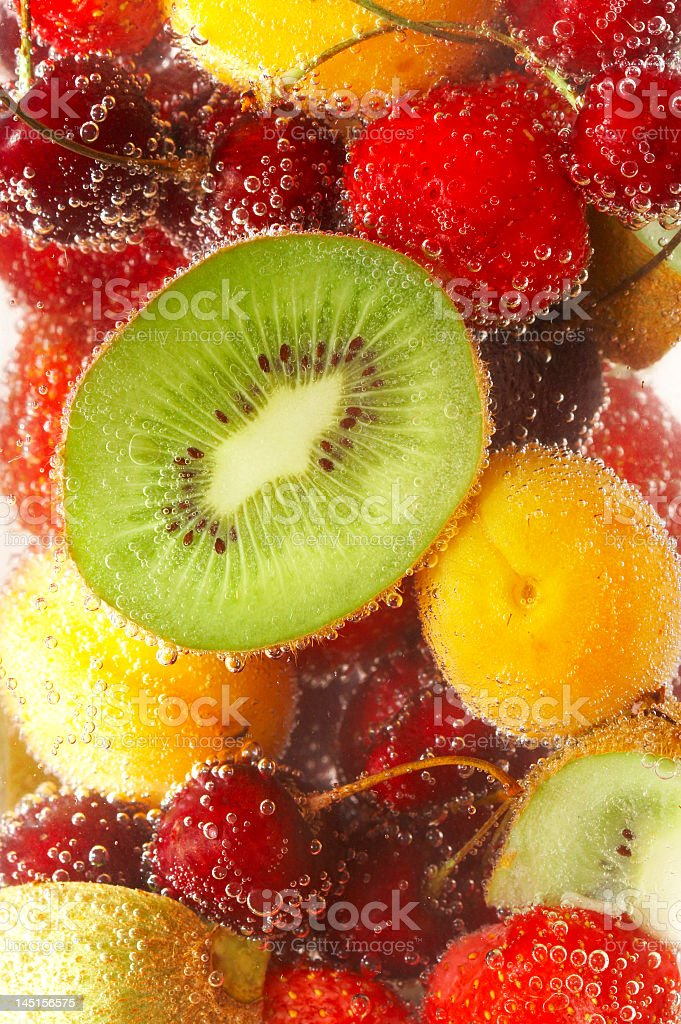 Close-up of kiwi, peaches and cherries with bubbles on fruit stock photo