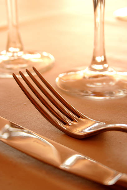 Close-up of knife and fork in front of wine glasses stock photo