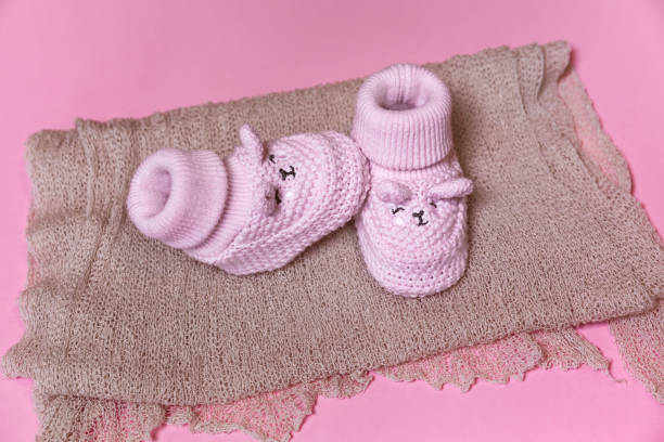 nahaufnahme von gestrickten häkeln neugeborenen schuhe, auf einem rosa hintergrund wartet auf ein baby-mädchen - babyschuhe nähen stock-fotos und bilder