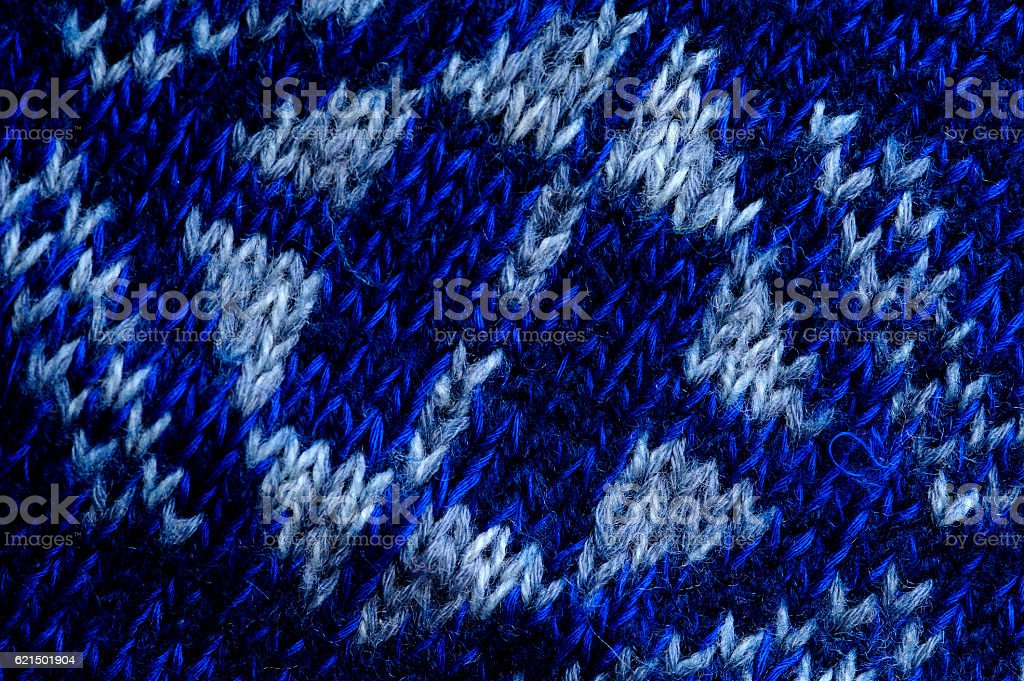 Closeup of knitted ornament on blue background Lizenzfreies stock-foto