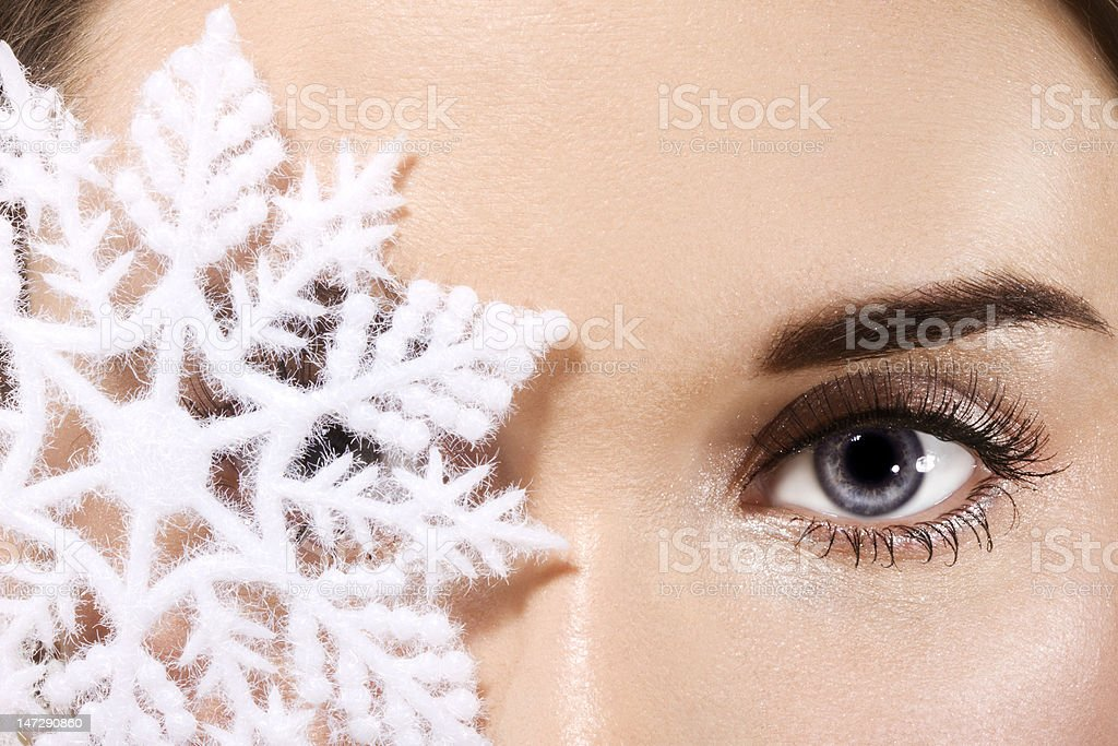 Close-up of large snowflake covering woman's eye royalty-free stock photo