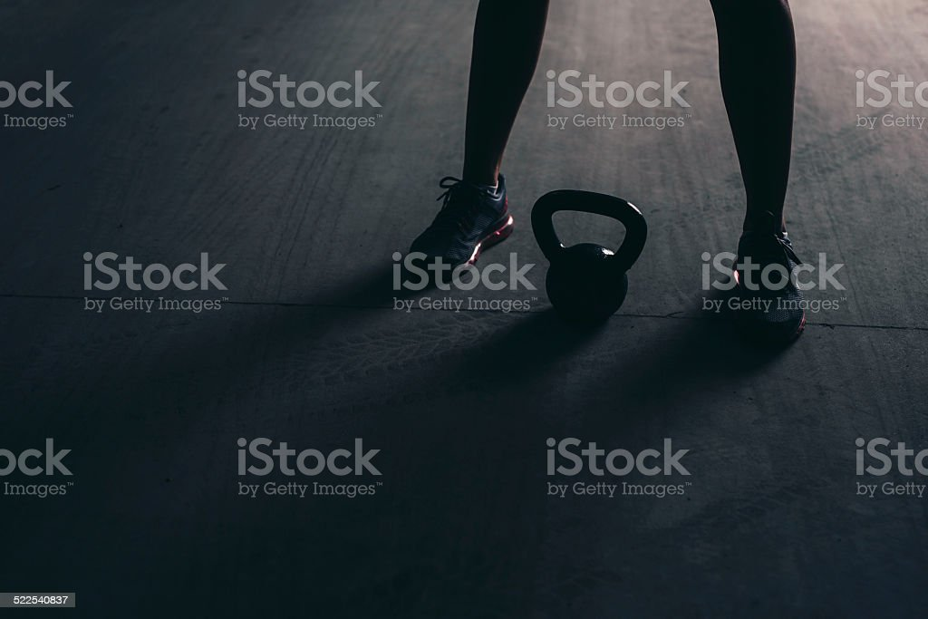 Close-up of legs and  kettlebell lying on a concrete floor stock photo