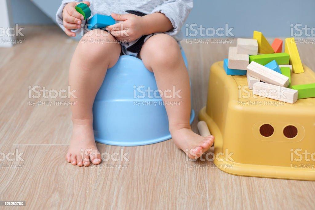 Closeup de pernas de giro asiáticos 18 meses de idade da criança bebê menino criança sentado no penico brincar com blocos de madeira brinquedo - foto de acervo