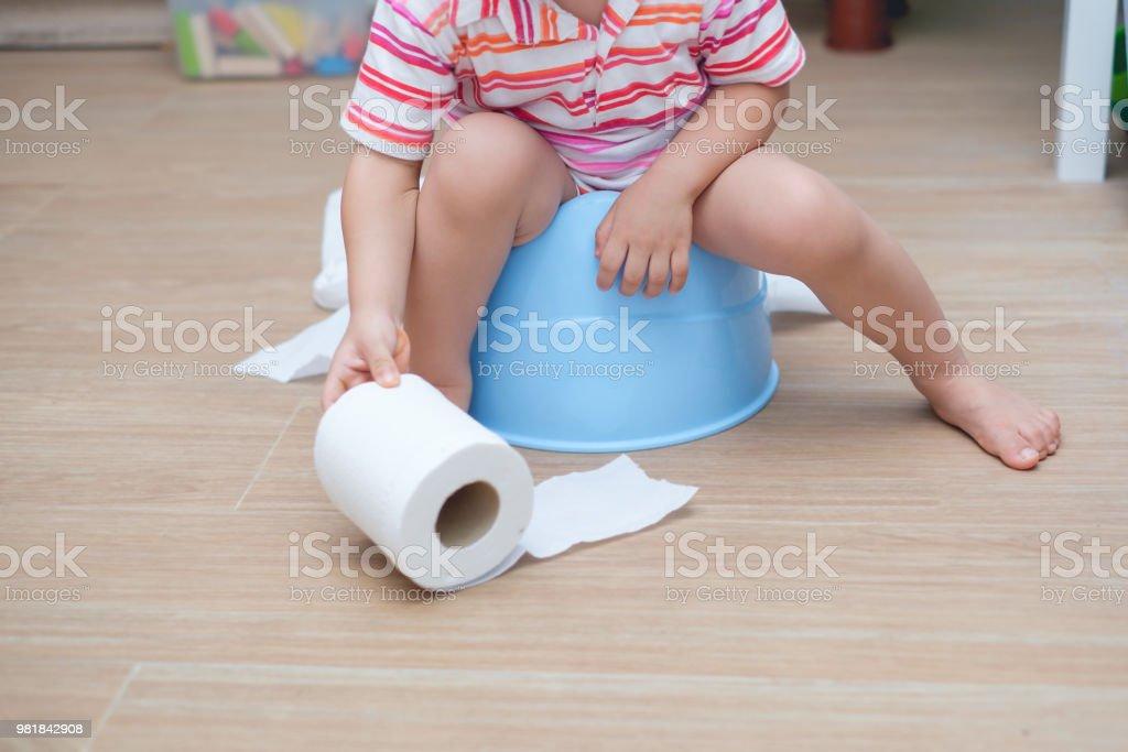 Closeup de las piernas de Asia 2 años niño bebé niño niño pequeño sentado en la bacinica azul sosteniendo, jugando con el papel higiénico - foto de stock
