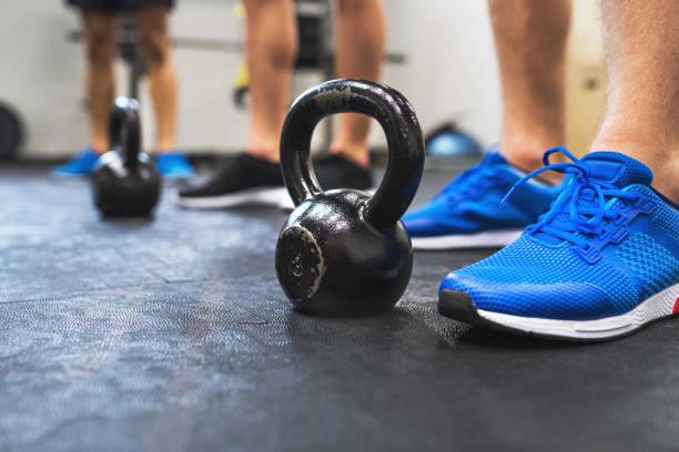 un primer plano de las piernas de tres hombres en pie de gimnasio por kettlebells. - pesa rusa fotografías e imágenes de stock