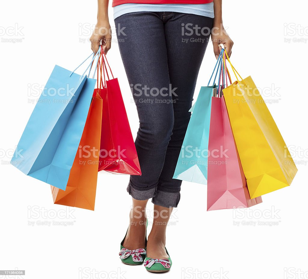 Close-up of legs of woman carrying colorful shopping bags stock photo
