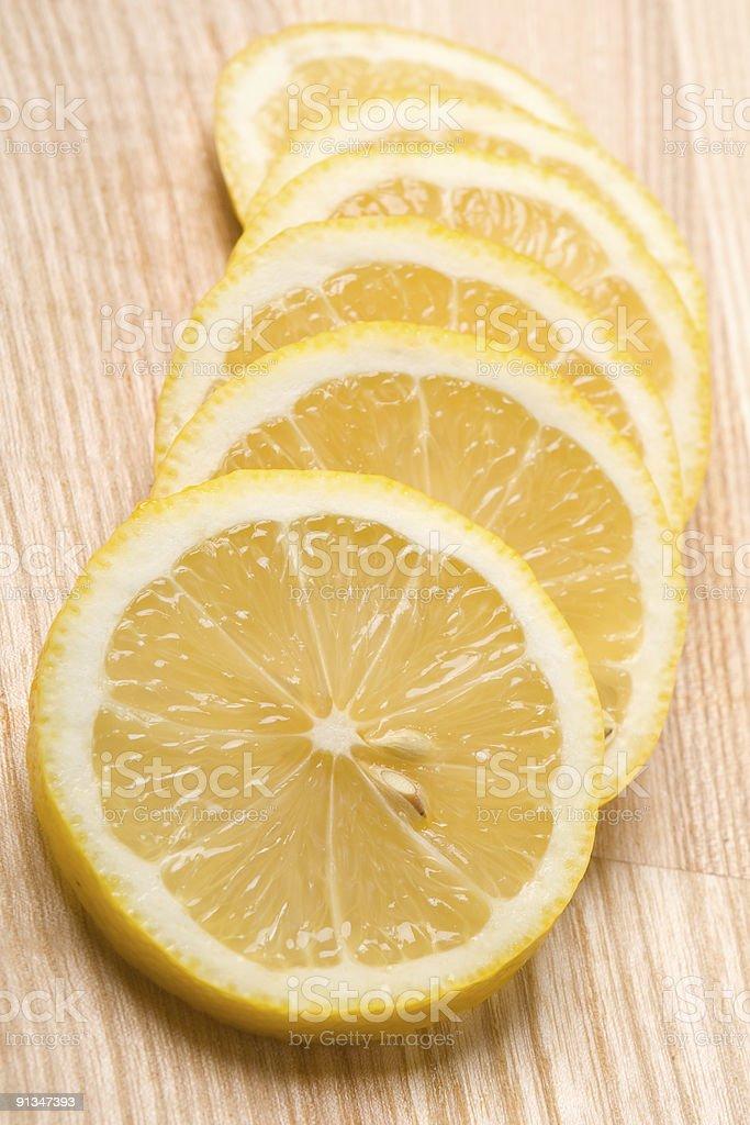 Closeup of lemon slices on cutting board stock photo