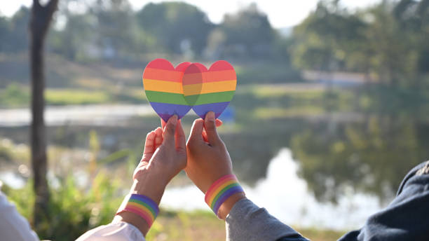 Closeup of LGBT couple while they are holding a rainbow hearts on hand. LGBT happiness concept. stock photo