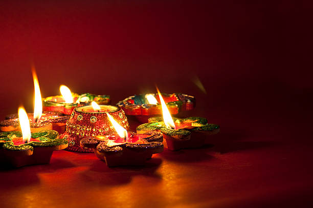 close-up of lit colorful candles on a wooden surface - diwali stock pictures, royalty-free photos & images