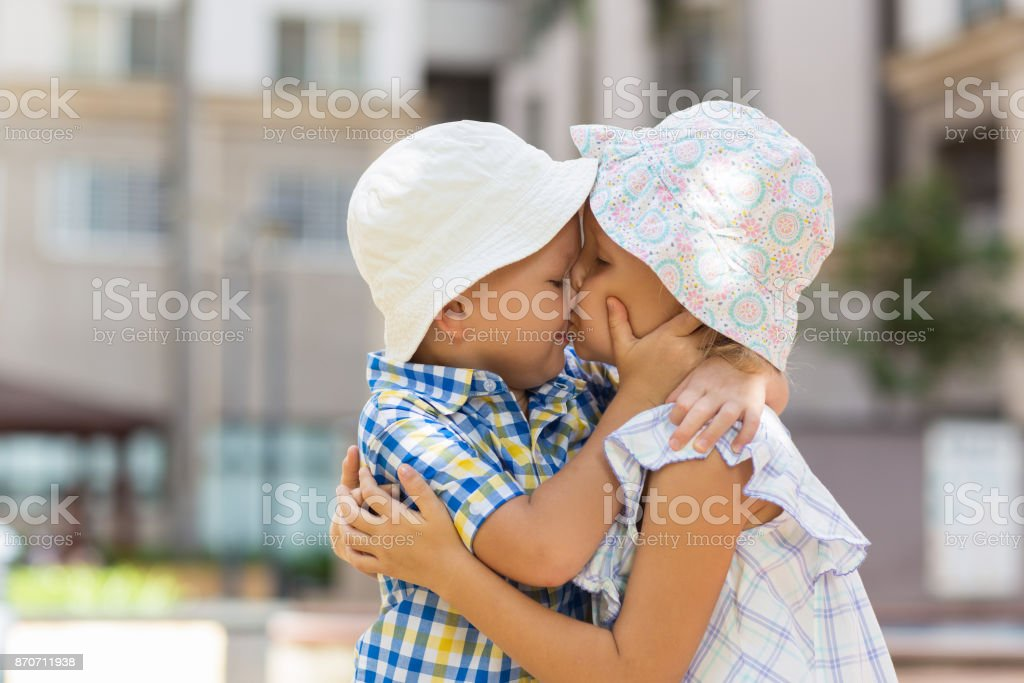 Closeup of Little Boy and Girl Hugging and Kissing stock photo