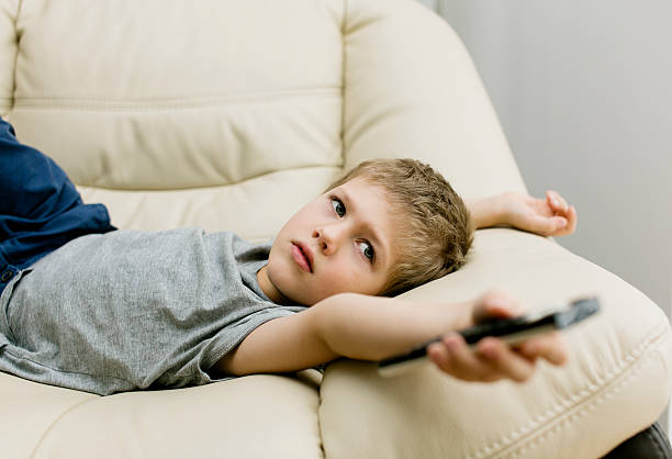 Close-up of little boy controlling remote control on couch stock photo