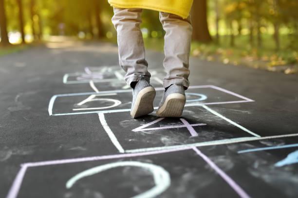 nahaufnahme der beine des kleinen jungen und hopscotch auf asphalt gezogen. kinder spielen hopscotch spiel auf spielplatz im freien an einem sonnigen tag. - himmel und hölle spiel stock-fotos und bilder