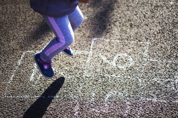 Closeup of little boy's legs and hopscotch drawn on asphalt. Child playing hopscotch game on playground outdoors on a sunny day. Summer activities for children. Kid playing hopscotch on playground outdoors. Little children playing hopscotch drawn chalk stock photo