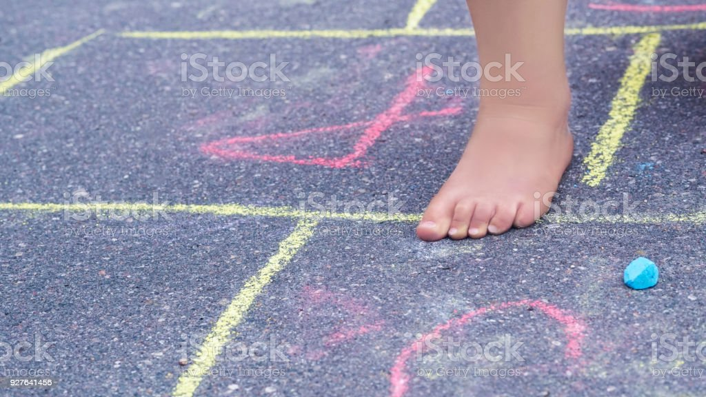 Closeup of little boy's legs and hopscotch drawn on asphalt. Child playing hopscotch game on playground outdoors. stock photo