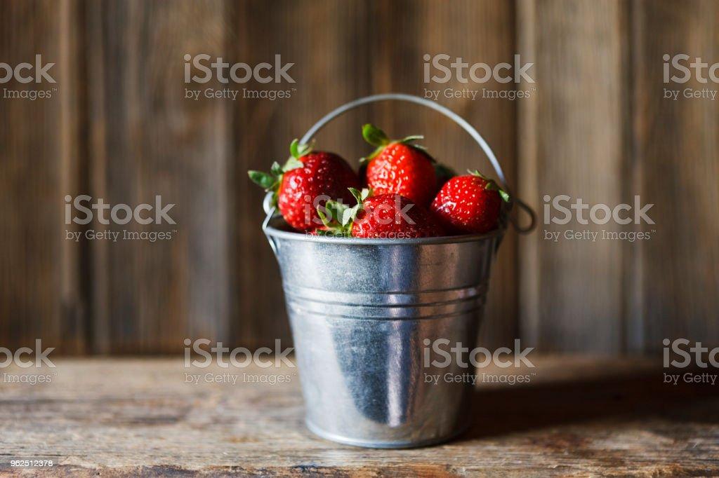 Close-up de pequeno balde com morangos frescos e suculentos sobre fundo de madeira vintage - Foto de stock de Agricultura royalty-free