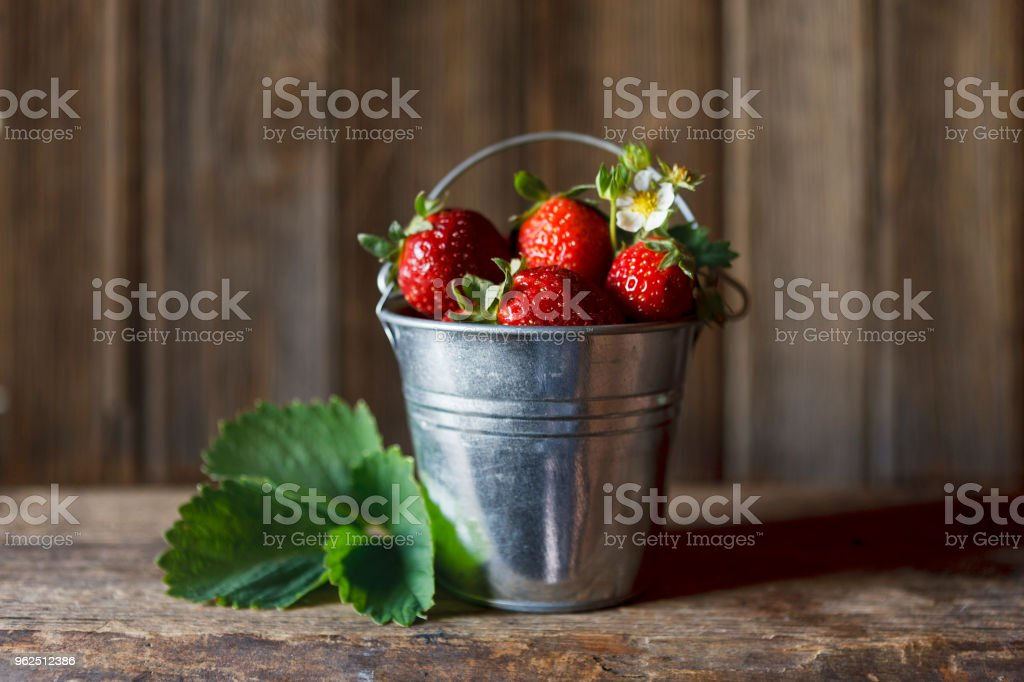 Close-up of little bucket with fresh and juicy strawberries on vintage wooden background - Royalty-free Agriculture Stock Photo