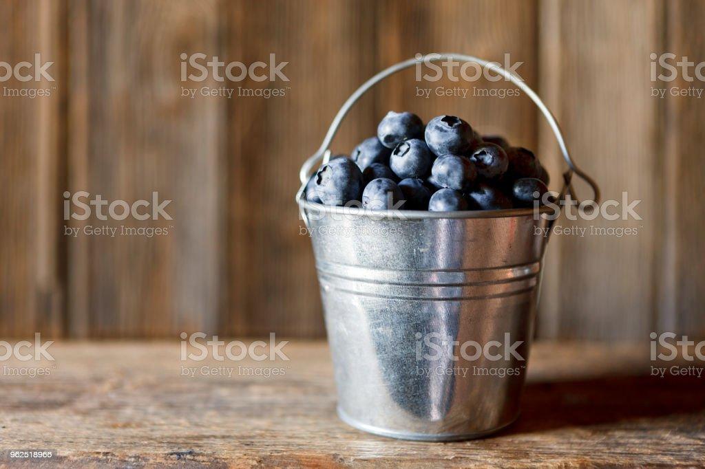 Close-up de pequeno balde com mirtilos frescos na mesa de madeira - Foto de stock de Agricultura royalty-free