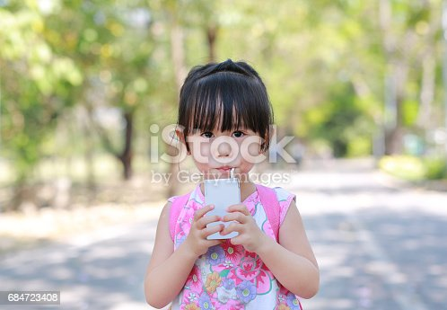 istock Closeup of little girl drinking milk with straw in the park. Portrait outdoor. 684723408