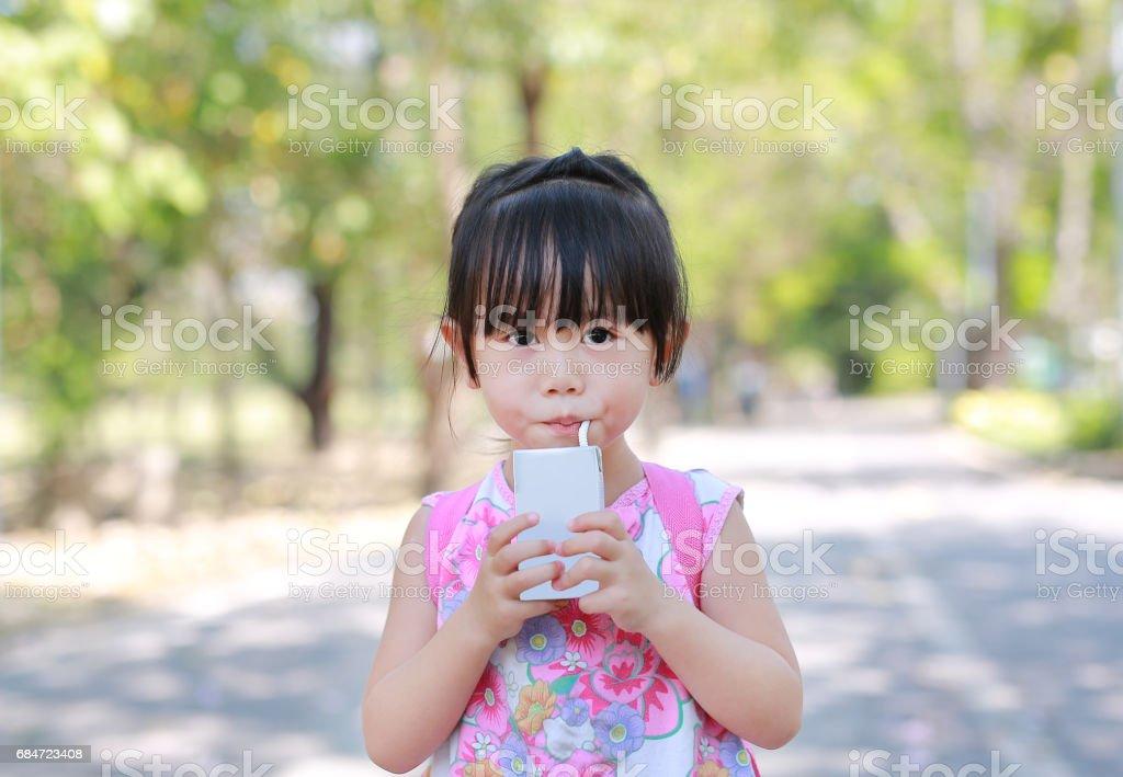 Primer plano de niña tomando leche con paja en el parque. Retrato al aire libre. - foto de stock
