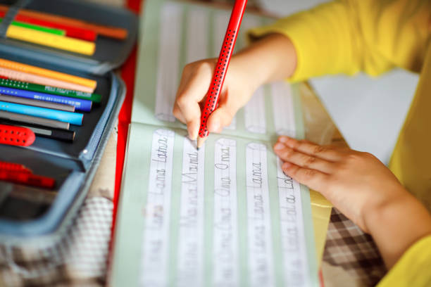 Nahaufnahme des kleine Kind junge zu Hause machen Hausaufgaben, Kind schreiben erste Buchstaben und Wörter wie Mama mit bunten Stiften. Schule und Bildung – Foto