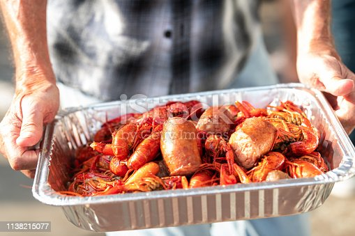 Closeup of lobsters and seafood with hands holding tray of red shellfish in New Orleans street food