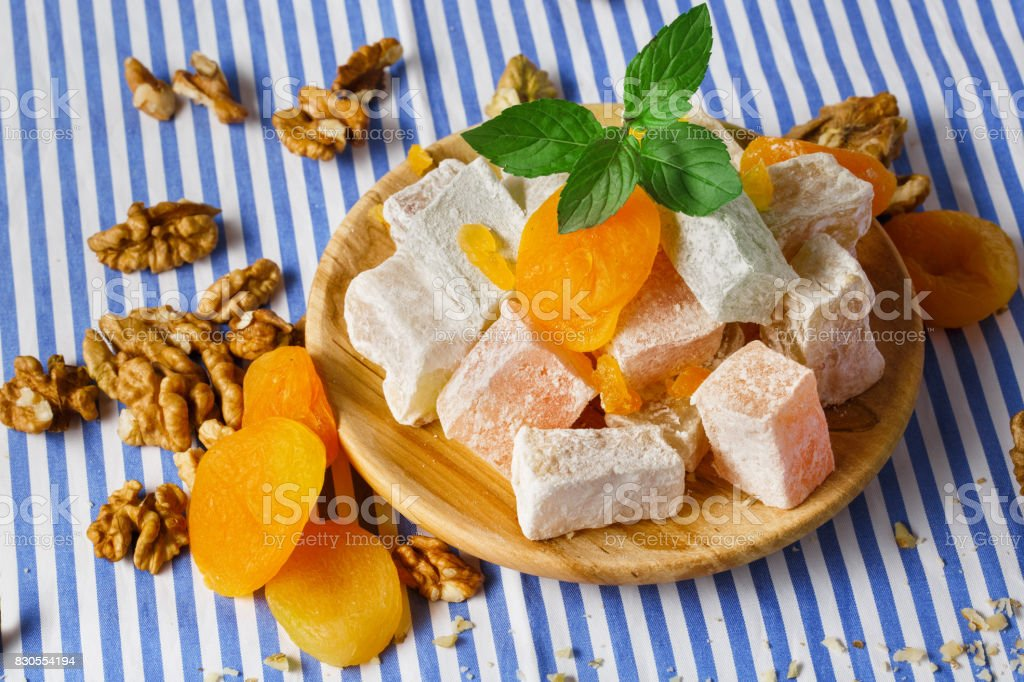 Close-up of lokum, dried apricots on a wooden plate with fresh leaves of mint and walnuts on a striped background. stock photo