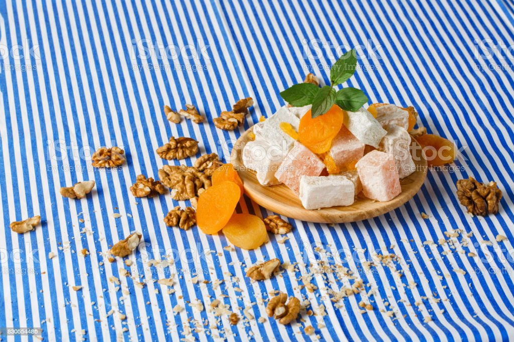 Closeup of lokum with vivid dried apricots, leaves of mint, walnuts and crumbs of nuts on a striped background. stock photo