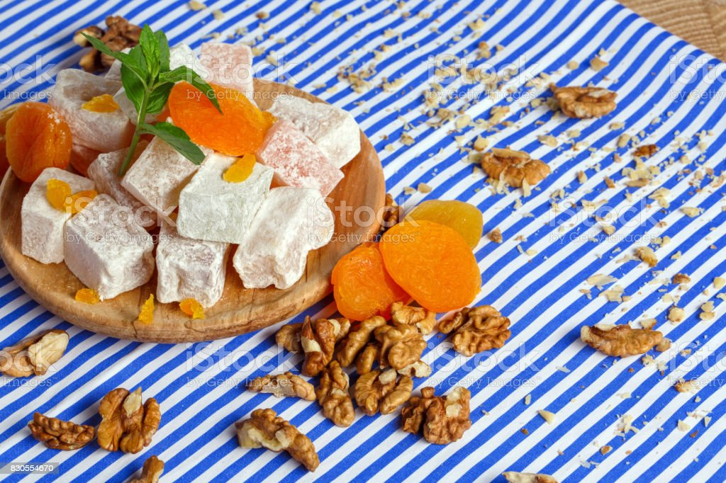 Close-up of lokum with vivid dried apricots, leaves of mint, walnuts and crumbs of nuts on a striped background. stock photo