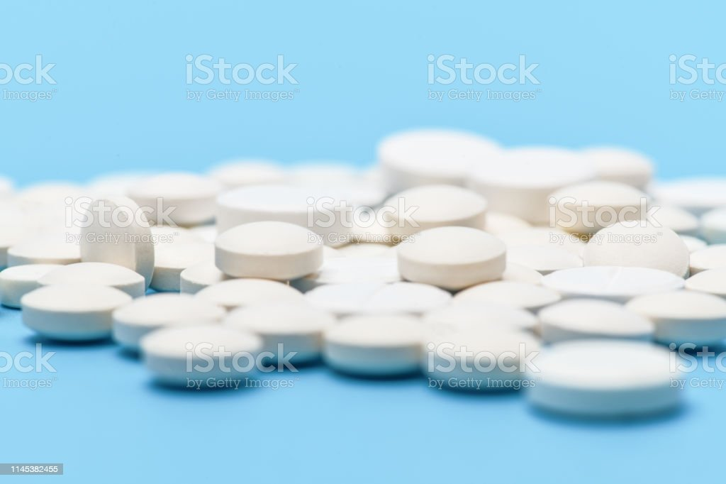 Close-up of lots of white round pills on blue background. Medical background Close-up of lots of white round pills on blue background. Medical background Antibiotic Stock Photo