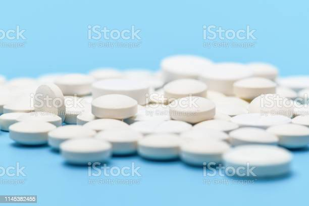 Closeup Of Lots Of White Round Pills On Blue Background Medical Background Stock Photo - Download Image Now