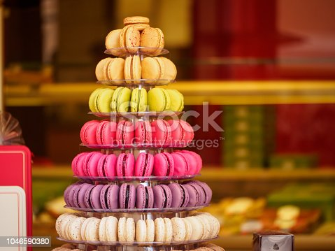 Closeup detail of multiple colorful macarons arranged on a tower at a French sweets and confectionery store. Shallow focus. Riquewihr, France. Travel and cuisine.