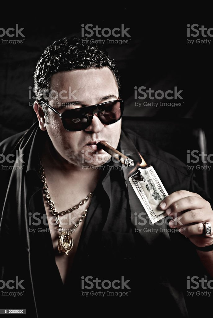 Close-up of mafia man's hand  burning  cigar with money stock photo