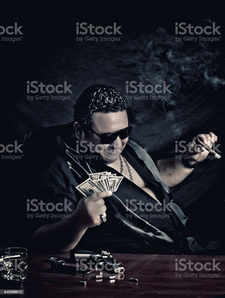 Close-up of mafia man's sitting on the chair counting money stock photo